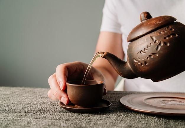 カップに暖かいお茶を注ぐ人