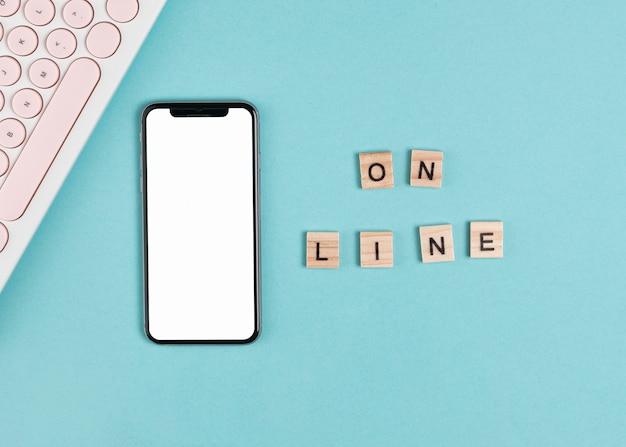Плоский телефон рядом с клавиатурой макет