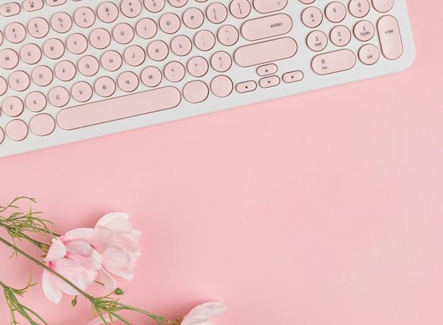 Клавиатура и цветы копией пространства