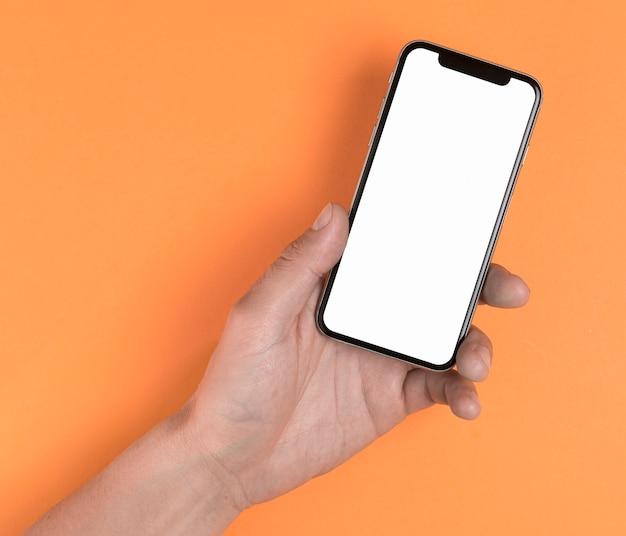 モックアップの黄色の背景に携帯電話を持っている手