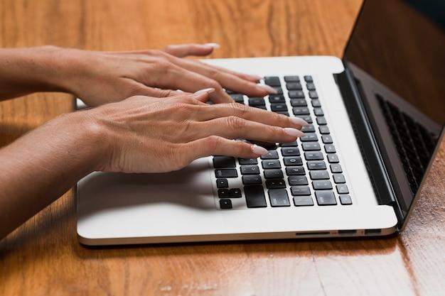 ラップトップに取り組んでいる女性の手