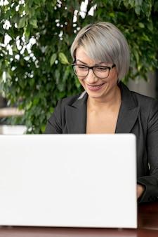 フロントビュービジネスの女性のラップトップに取り組んで