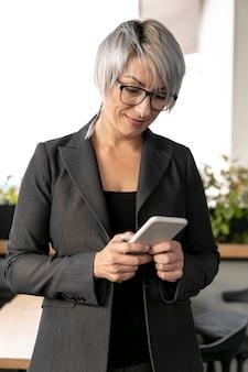 Деловая женщина в офисе, проверка мобильного