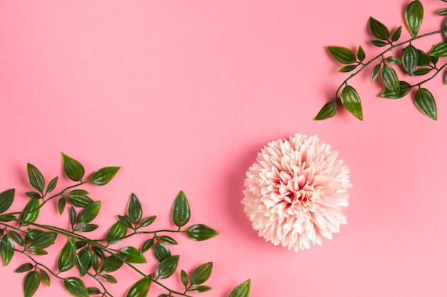 葉の枝とピンクの花