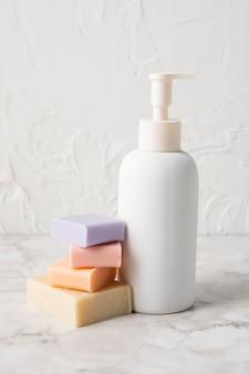 Разноцветное мыло рядом с пластиковой бутылкой