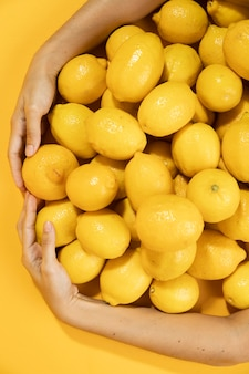 Рука крупного плана, окружающая сырые лимоны