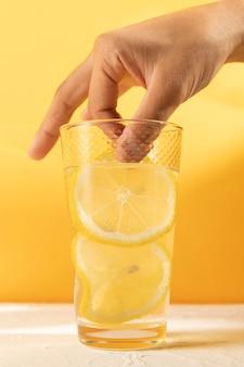 レモネードの新鮮なガラスとクローズアップ手