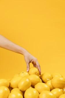 Рука трогательно лимоны с копией пространства