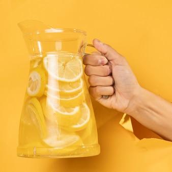 レモネードの瓶を持っているクローズアップ手