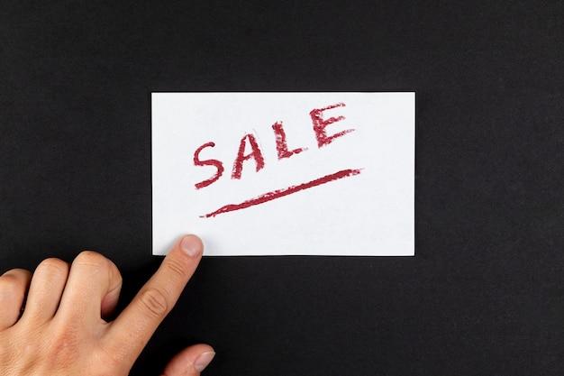 Рука показывает слово продажа написано на бумаге