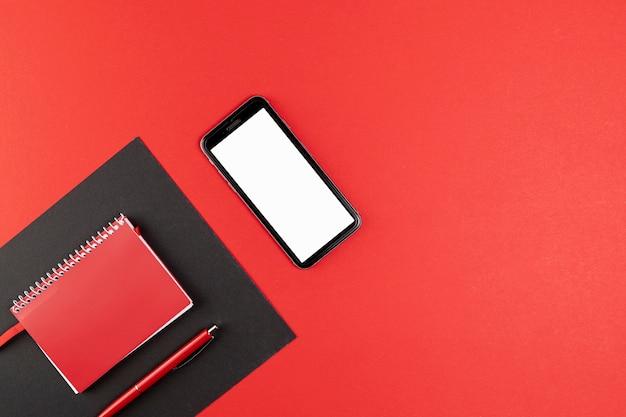赤いノートブックの横にモックアップの電話