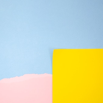 青いコピースペース背景と抽象的な黄色とピンクのポストイット