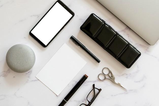 机の上の携帯電話のモックアップフラットレイアウト