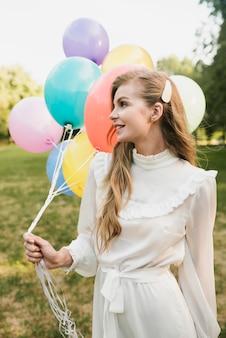 Вид спереди элегантная молодая женщина с воздушными шарами