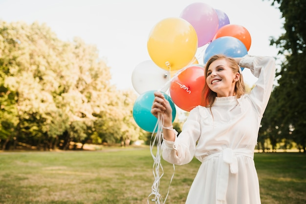 Улыбающаяся девушка в парке держит воздушные шары