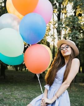 Женщина вид спереди в шляпе держит воздушные шары