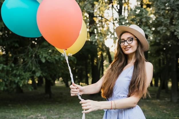 Улыбающаяся девушка с воздушными шарами смотрит в камеру