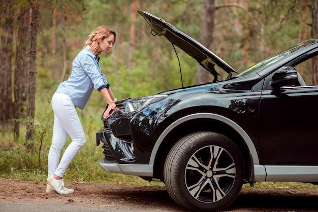 車をチェックする女性のフルショット