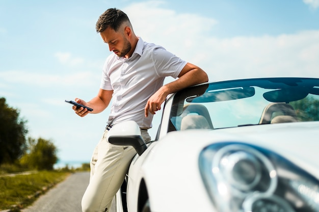 Мужчина смотрит на телефон среднего снимка