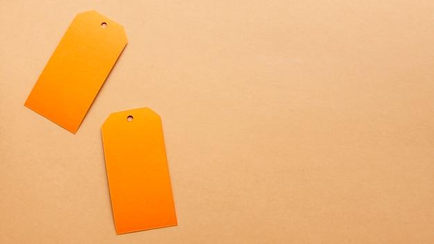 コピースペースを持つ中立カーボードシート上のオレンジ色のタグ