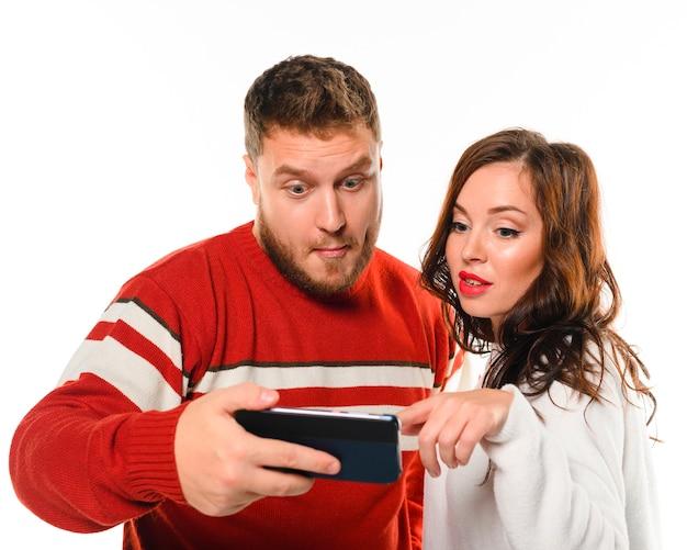 Милые зимние модели смотрят на телефон