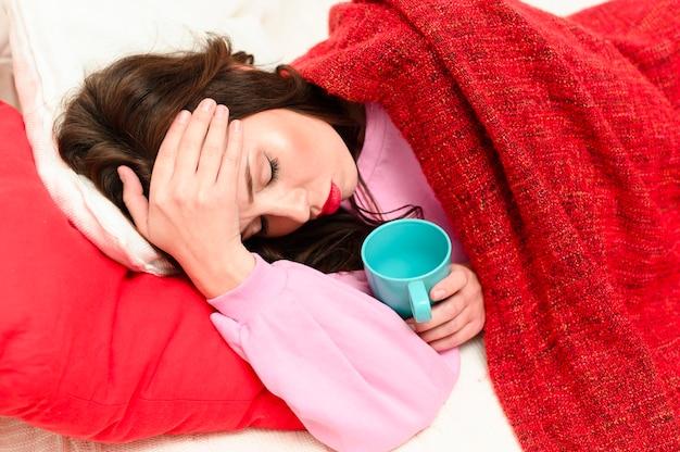 ベッドに滞在しながら頭痛を持つ女性
