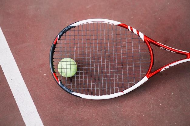 Высокий угол теннисный мяч с ракеткой рядом