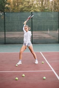Вид спереди молодая самка играет в теннис
