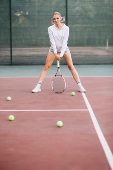Низкий угол женщина играет в теннис