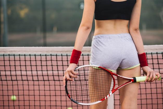 フィールドでテニスをしているクローズアップの若い女性