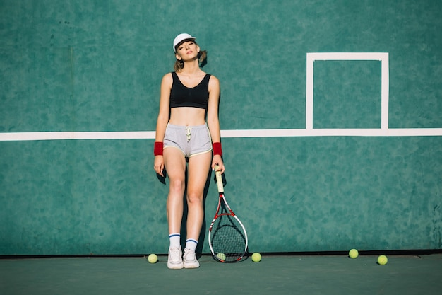 テニスコートでスポーツウェアの運動女性