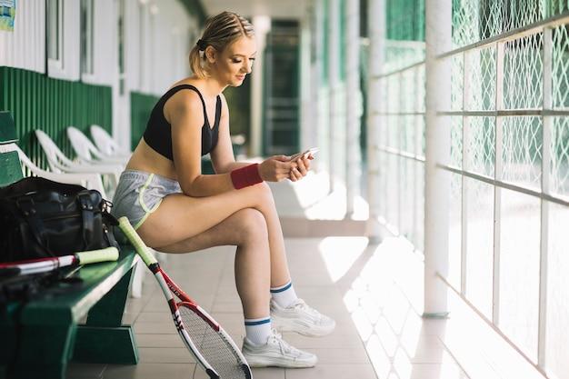 Теннисистка проверяя ее телефон женщины