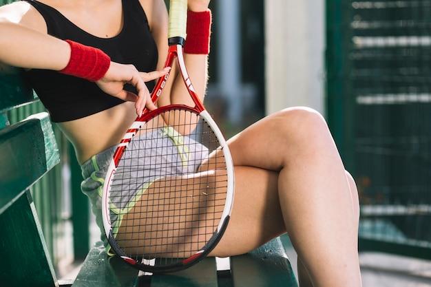 彼女のテニスラケットを保持している陽気な女性