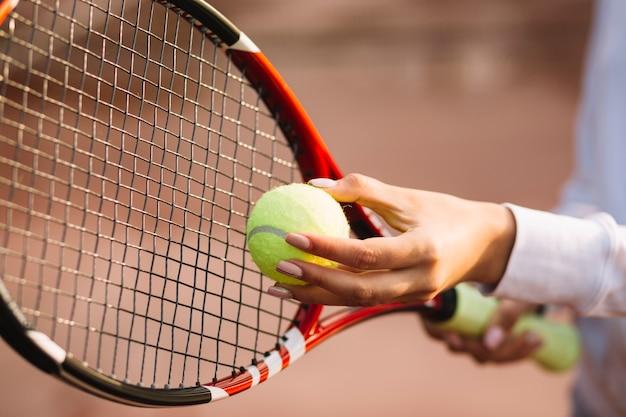 Женщина держит теннисный мяч и ракетку