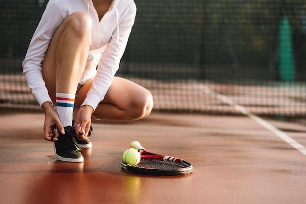 Женщина завязывает шнурки перед тренировкой