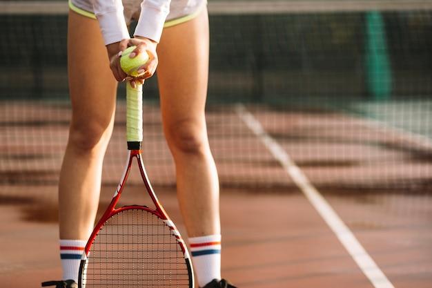 陽気な女性はテニスラケットにかかっています。