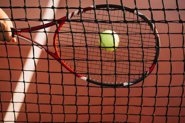 テニスプレーヤーがネットにボールを打つ