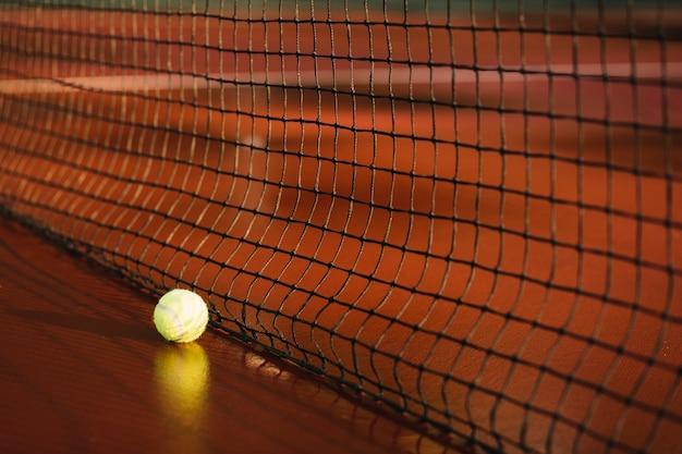 テニスネットの近くのテニスボール