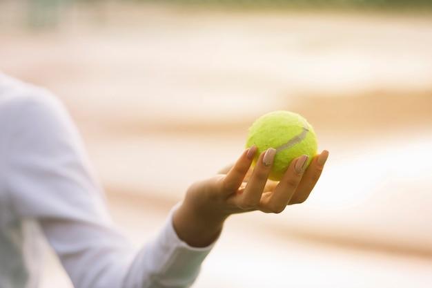 手でテニスボールを保持している女性