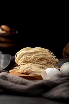 黒い背景に木製のサポートの麺