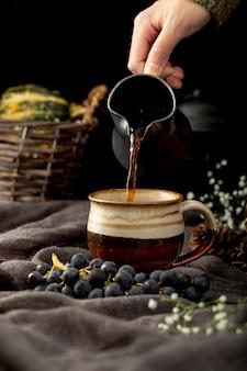 Мужчина наливает кофе в коричневой чашке