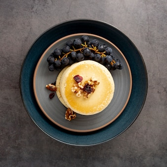 Синяя тарелка с блинами и виноградом на сером фоне