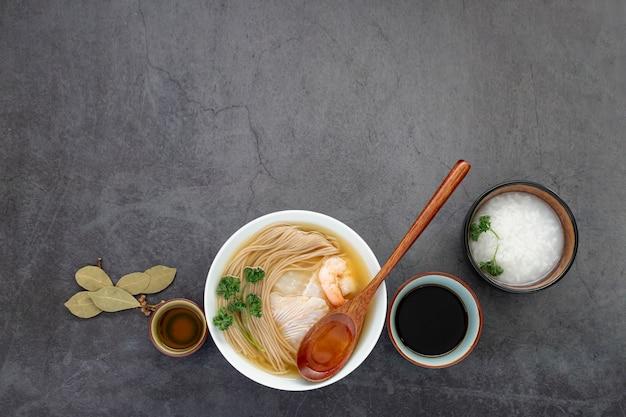 Белая миска с супом с лапшой на сером фоне