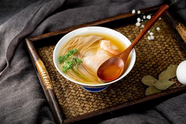 木製のテーブルに木製のスプーンで麺スープボウル
