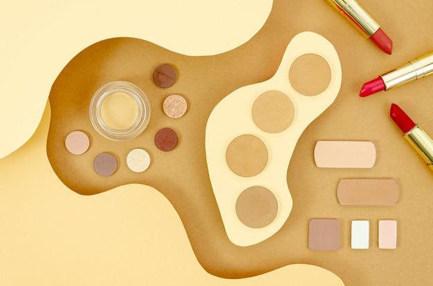 ベージュ色の背景に女性のメイクアップ製品