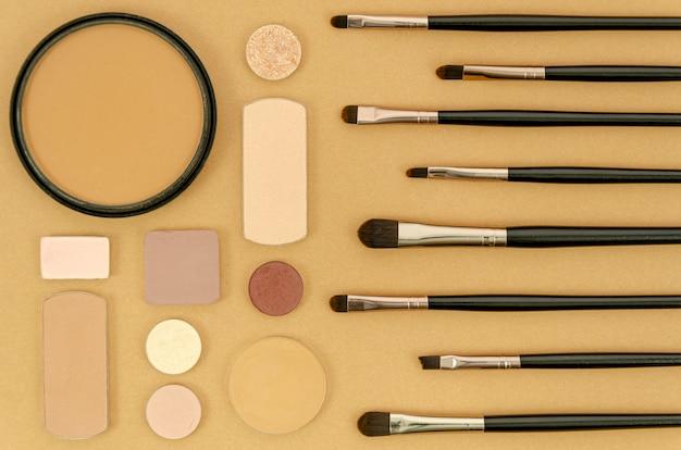 Различные кисти и макияж на бежевом фоне