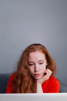 若い女性自宅でラップトップで読書