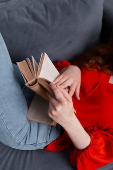 ソファの読書に高角度のクローズアップ女性