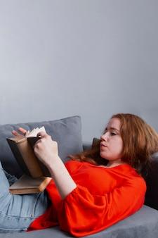 Вид спереди молодая девушка на домашнем чтении