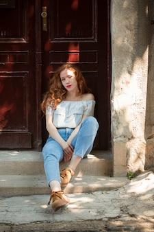 赤毛の女の子がドアの前でポーズ